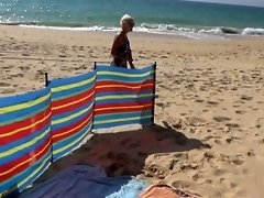 Naked blonde on a public nudist beach playing with a vibrator video on WebcamWhoring.com